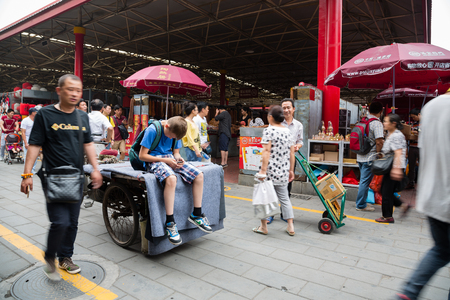 trishaw: BEIJING - CIRCA JUNE, 2015: European boy sitting on a trishaw and uses smartphone being on the Panjiayuan Antique Market - one of best antiques market in China. Area shopping area of square meters Editorial