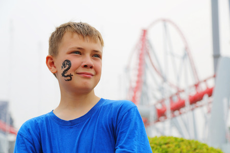 switchback: Portrait of a boy on the background of a roller coaster at an amusement park.  Drawing a dragon on her cheek. Stock Photo