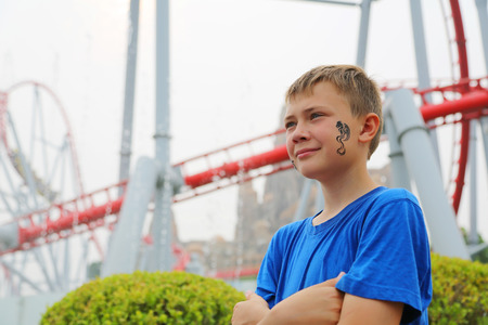 switchback: Boy on a background of a roller coaster at an amusement park. Drawing a dragon on her cheek.