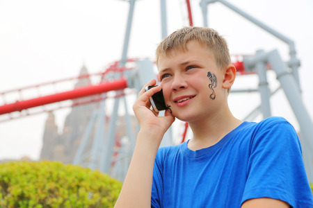 switchback: Cute boy talking on a cell phone at an amusement park. Drawing a dragon on her cheek.