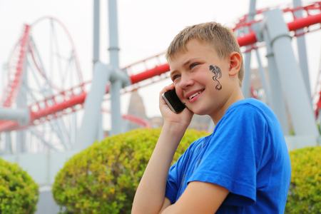 switchback: Boy talking on a mobile at an amusement park. Drawing a dragon on her cheek.