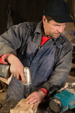 planos electricos: Carpenter working with a drill in the carpentry workshop. Focus on tool.