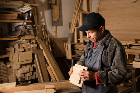 planos electricos: Carpenter works with wood in the carpentry workshop. Focus on wooden part. Foto de archivo