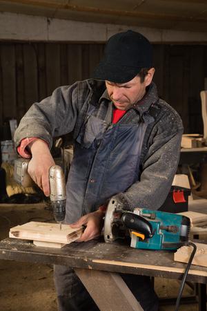 planos electricos: Carpintero que trabaja en un taller con un taladro.
