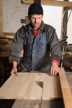 planos electricos: Carpenter serrar una tabla en la circulación vio en el taller de un carpintero.