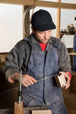 planos electricos: Carpintero trabaja con madera en el taller de carpintería.