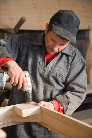 furniture part: Carpenter drills with a drill hole in the part of furniture.