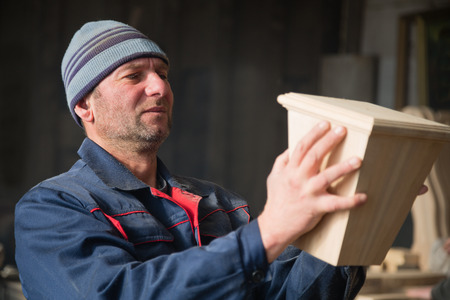 Joiner inspecting wood furniture part in the carpentry workshop