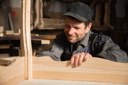 carpenter: Smiling carpenter examines produces furniture in the workshop Stock Photo