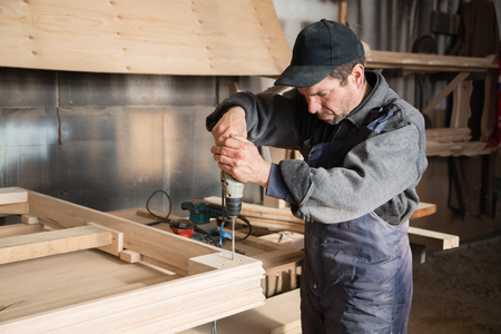 Carpenter assembles wooden furniture in the carpentry shop. Focus on the hand drill. Stock Photo