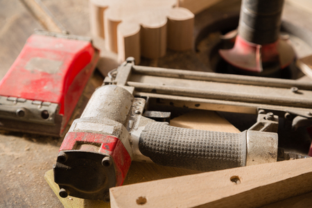 sander: Carpentry tools - nailing gun and sander on a workbench Stock Photo
