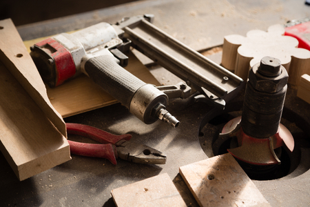 nailing: Carpentry tools - gun nailing and pliers lie on a workbench