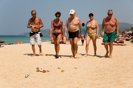 boules: KARON BEACH, THAILAND - CIRCA FEBRUARY, 2015: European tourists are playing the French game boules (petanque). Karon beach is one of the most popular beaches among tourists in Phuket