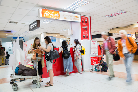 tourism industry: PHUKET ISLAND, THAILAND - CIRCA FEBRUARY, 2015: People at the payment counter of Air Asia in terminal of Phuket International Airport. Airport plays an important role in tourism industry of Thailand Editorial