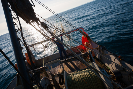 cordage: Fishermen standing at the stern of small fishing vessel. Sea of Japan.
