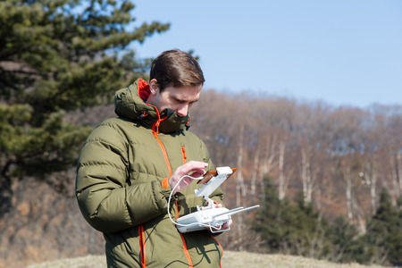 flying man: Man controls the flying drones in the spring