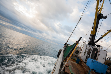 trawl: Small fishing boat floating on the sea in the early morning. Sea of Japan.