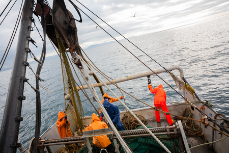 commercial fisheries: Fishermen in waterproof clothing on the deck of the fishing vessel. Morning time.