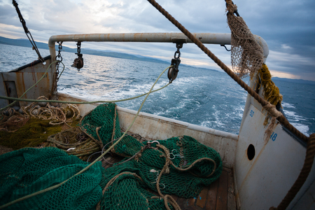 commercial fisheries: Fishing nets are on the deck of a small fishing vessel. Evening time.