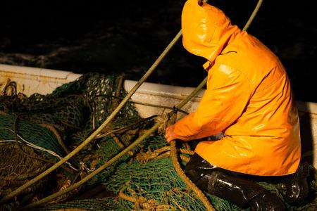 trawl: Trawl master repairs fishing trawl. Night time. Stock Photo