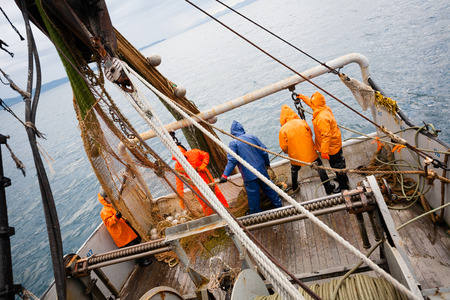 Fishermen in protective suits on deck Fishing vessel. Morning time. Stock Photo