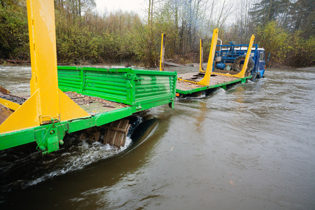 trackless: Heavy-duty truck for transportation of logs stuck in the river. Autumn rain. Russian Far East.