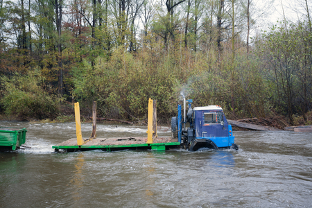 trackless: Heavy-duty truck fording the river at high water. Autumn rain. Russian Far East. Stock Photo