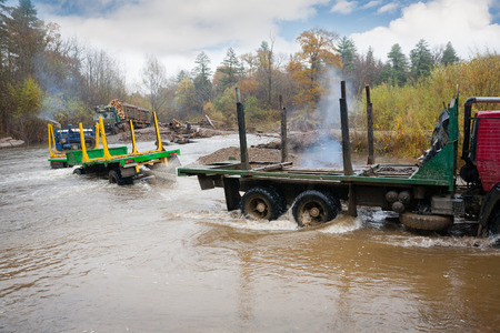trackless: Heavy-duty truck towing the trailer stuck in river. Autumn rain. Russian Far East.