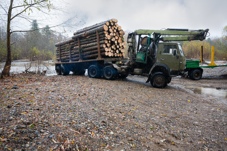 roadless: Heavy truck for transportation of logs standing on the bank of the river. Autumn rain. Russian Far East.