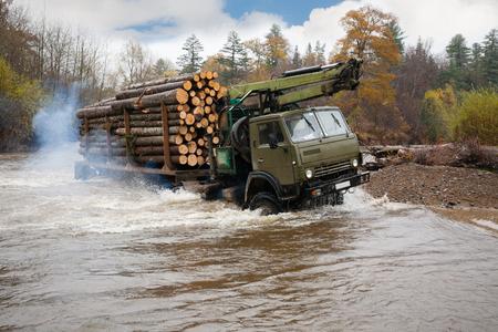 lejos: camiones pesados ??para el transporte de troncos mueve vado en el río. Lluvia de otoño. Lejano Oriente ruso.