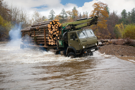 trackless: Heavy truck for transportation of logs moves ford in the river. Autumn rain. Russian Far East.