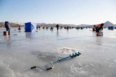 lejano oriente: tornillos de hielo Pescador en el primer plano, la pesca ol�an en Rusia. Krai de Primorie, Lejano Oriente. Foto de archivo