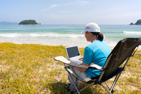 aged business: Middle-aged woman uses a laptop while on the beach on a summer day Stock Photo