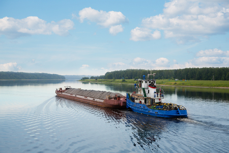 navigable: River tugboat moves cargo barge on the Volga river in the summer navigation.