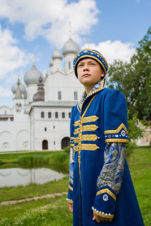 Muchacho en el juego ruso nacional Edad Media en el fondo de la catedral cristiana en Rostov Kremlin Grande (Veliky)