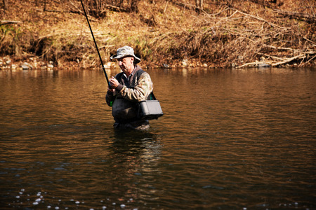 Fisherman holding a grayling caught in the river