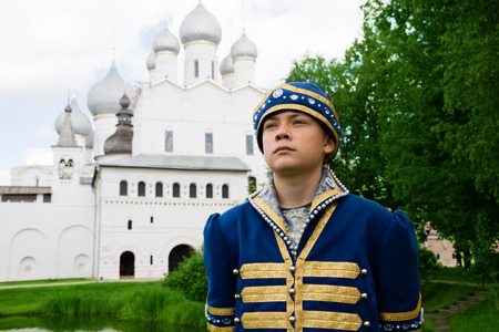 Teenager in national russian suit Middle Ages on the territory Kremlin Rostov Great (Veliky)