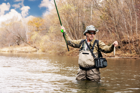 salmon falls: Fisherman holding a grayling caught in the river  Stock Photo