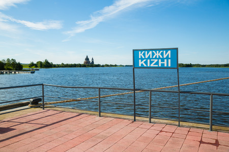 english famous: Pier on the famous island of Kizhi in Lake Onega in Karelia in the north of Russia. Inscription on the banner Kizhi on the Russian and English languages.