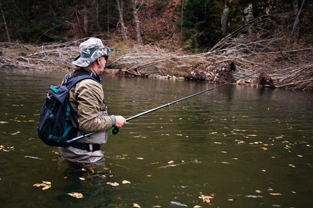 salmon falls: Fascinated by a fisherman fishing in the river is waiting for the catch Stock Photo