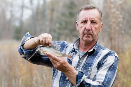 grayling: Joyful fisherman demonstrates caught grayling in autumn