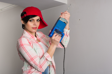 Young pretty woman with an old builder with a drill photo