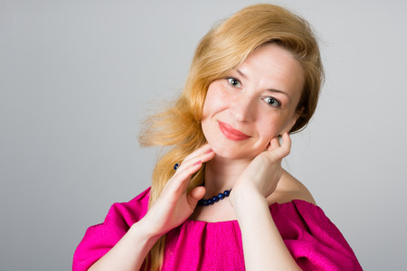 Portrait of a 39 year old woman in a pink dress Stock Photo