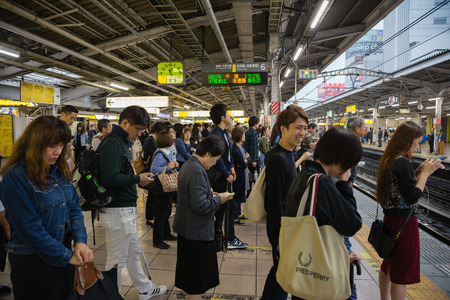 TOKYO - CIRCA MAY, 2017: People using smartphones on the platform waiting for the JR train, the railway in Tokyo is the main means of transporting passengers. Focus on the clock. Редакционное