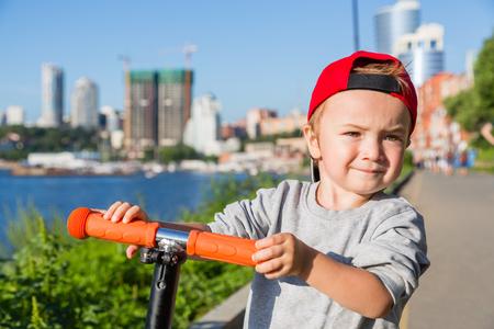 Happy little preschooler boy riding a scooter on the embankment in Vladivostok Russia