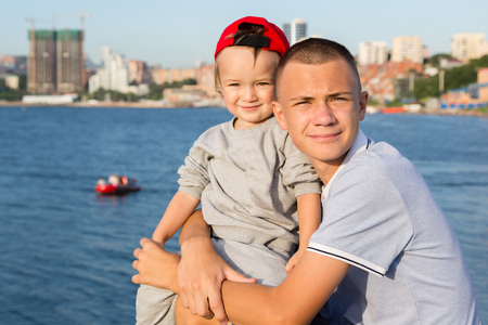 Eldest and younger brothers are resting on the embankment in Vladivostok, Russia.