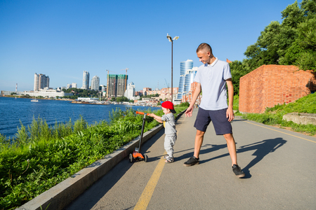 Older brother teaches younger brother to ride a scooter. Embankment in Vladivostok, Russia.