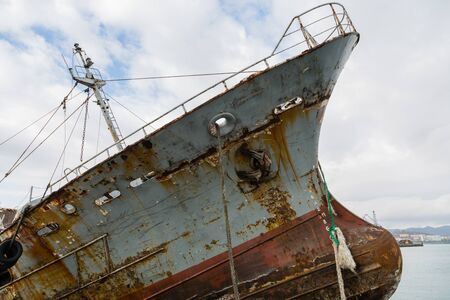 Bow and bulb of an old abandoned ship with an anchor. Environmental pollution.