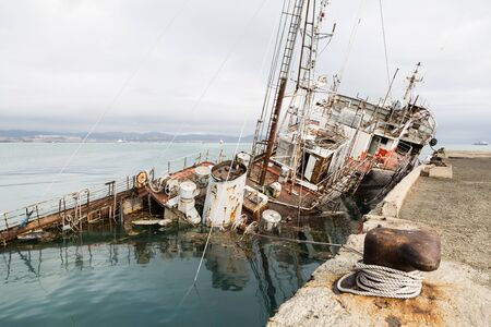 An old fishing boat sunk at a pier in the seaport. Environmental pollution.