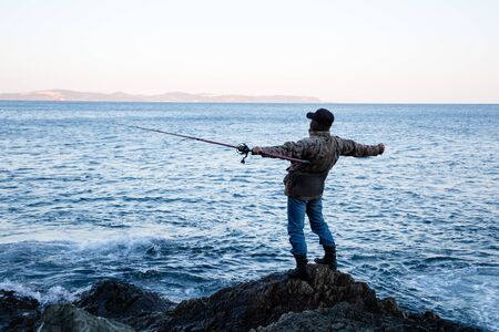 Fisherman admires the open spaces in the early morning Stock Photo